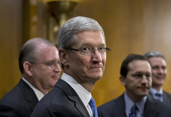 Apple CEO Tim Cook  (centre) is surrounded by his team during a break from testifying on Capitol Hill in Washington. (Pic: AP Photo/J. Scott Applewhite)