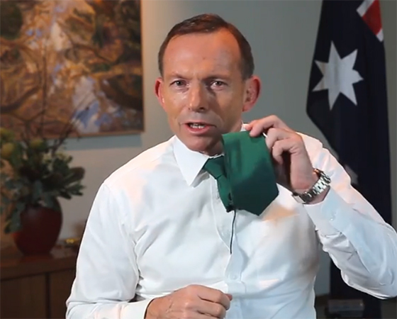 Prime Minister Tony Abbott waves his green tie during a video message for St Patrick's Day.